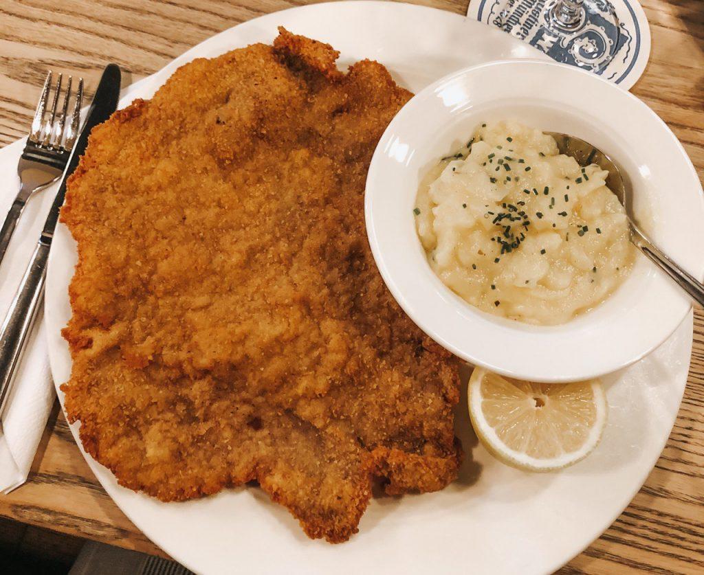 wiener schnitzel, la tradizionale cotoletta gigante servita con insalata di patate