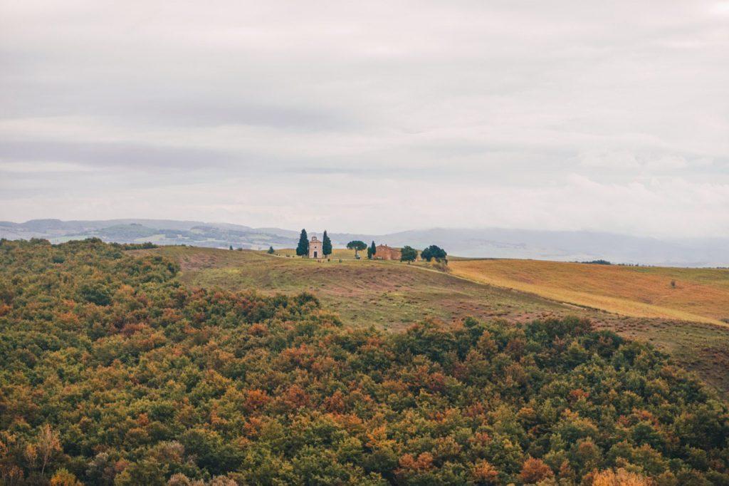 chiesa su una collina tra campi, alberi e vigneti