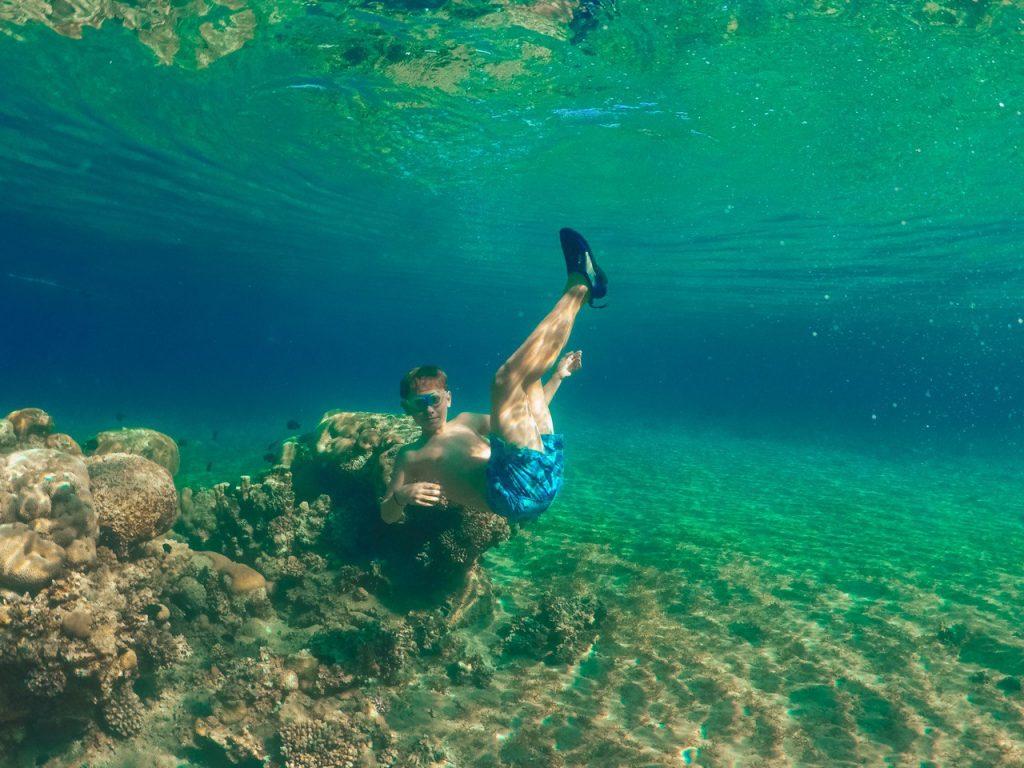 ragazzo nuota vicino alla barriera corallina