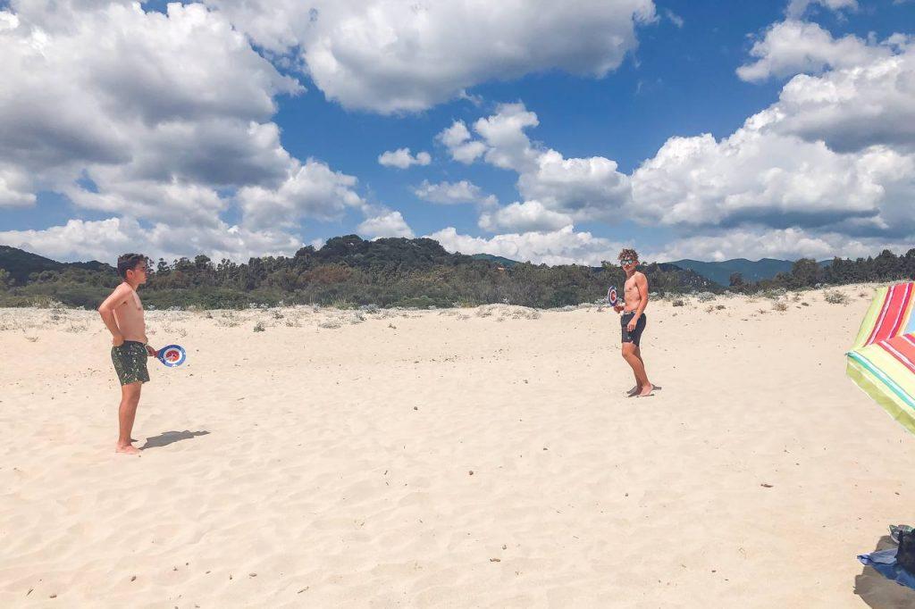 due ragazzi giocano a racchettoni in spiaggia