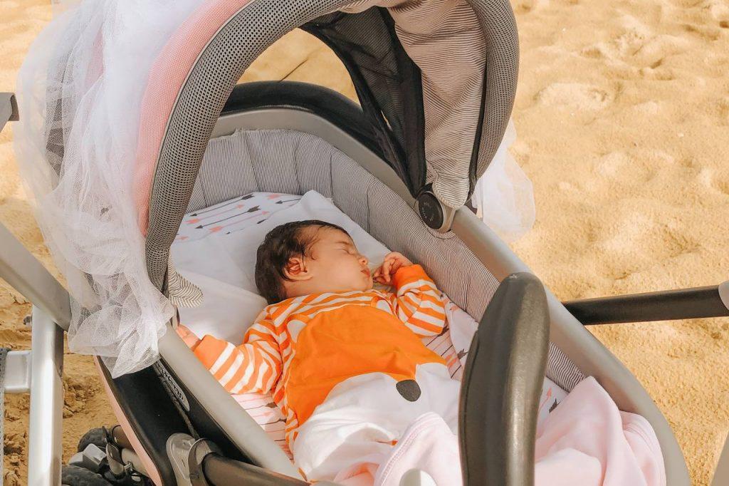neonata in carrozzina in spiaggia